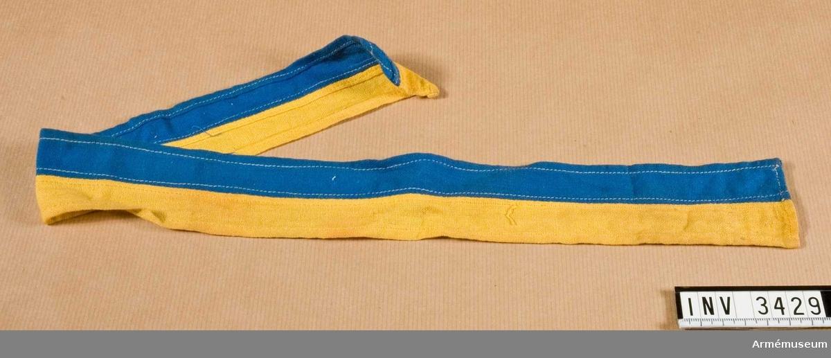 Längd: 590 mm, Bredd: 45 mm. Bindel för stridsdomare. Av gul och blå flaggduk i bomull. Maskinsydd.  Samhörande gåva: 3426-3429.