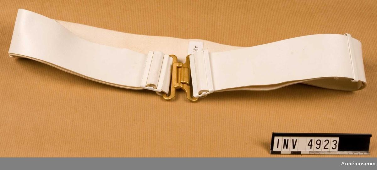 Av vit, vävburen plast. Ställbart med vita beslag och mattförgyllt spänne.  Samhörande nr är AM.4860-4925 (4920-4923)