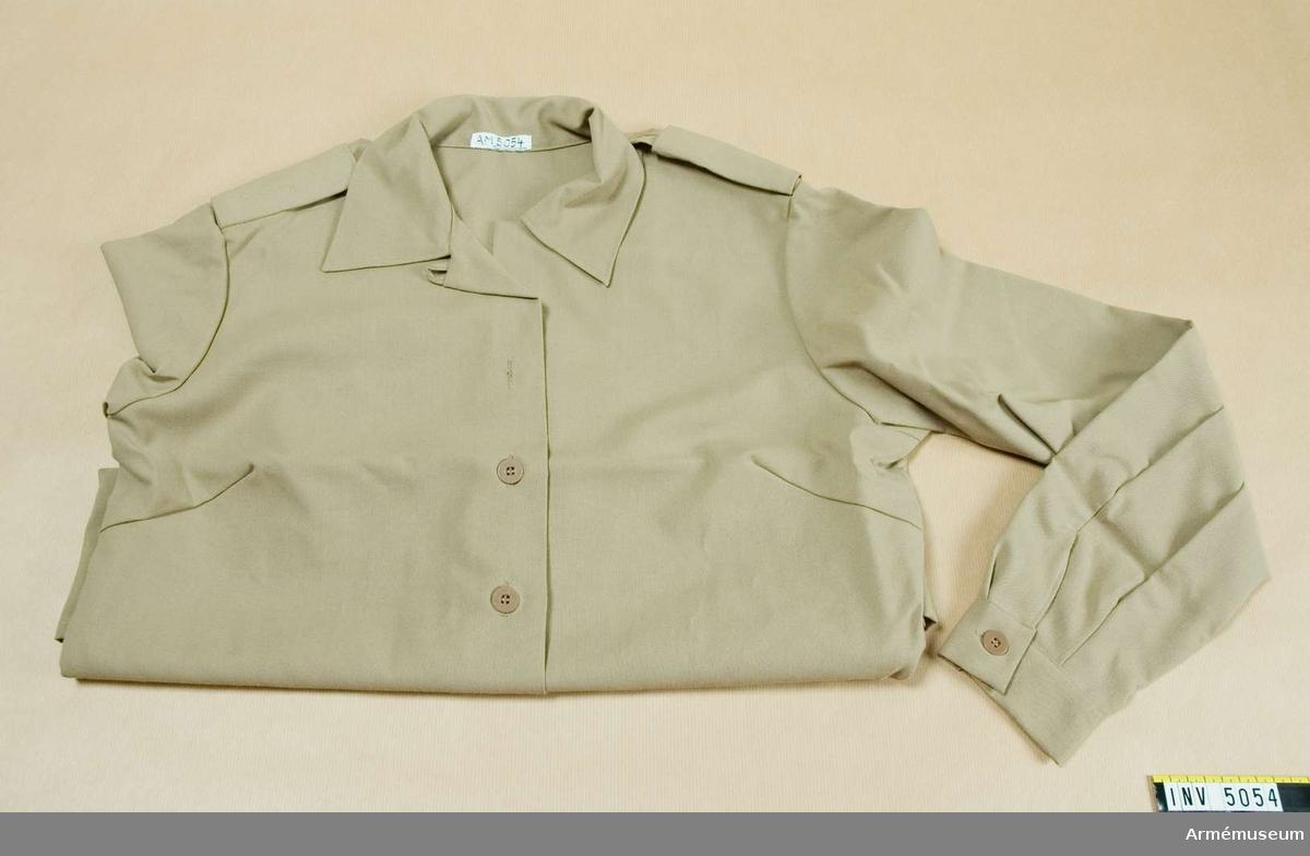 Blus m/1969 kv. Storlek 40. Tillverkas av beigefärgat syntettyg, har mjuk nedvikt krage, långa ärmar och fasta axelklaffar. Källa: UNIA 1977 6:218.