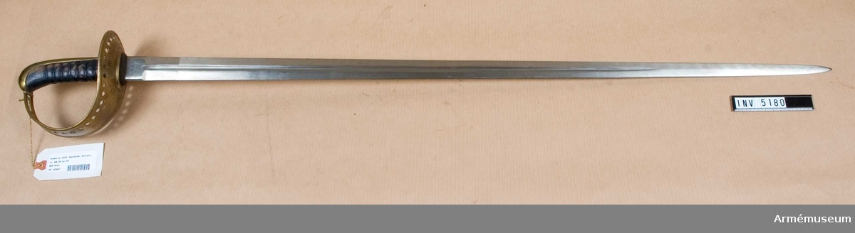 Samhörande nr är AM 5180 o AM 5181.Sabel m/1893, manskap, kavalleri.Hel längd 1195 klingans längd 941 mm, klingans bredd vid fästet 35 mm. Vikt 1080 mm. Klingan märkt J.B. GM. G.E.Svalling Rosenfors. (4 R. 4 S. No 46.).Fästet av mässing. Läderklädd kavel, vilken har åtta refflor och nedtill omgives av ett 10 mm brett mässingsbeslag. Kaveln har ryggbeslag, vilket upptill övergå i en låg kappa, som upptill har en låg nitknapp kring tångänden. Parerplåtens och handbygelns kanter äro på utsidan förstärkta och upphöjda. Längs dessa kanter går på vardera sidan från parerplåtens bakre kant till ungefär på handbygelns övre krök en rad på 37 hål. Ovanför det översta hålparet sitter ett ensamt hål. I handbygelns övre del litet framför kappan finnes ett avlångt hål för handremmen. Klingan tvåeggad med en blodrand.Samhörande är AM 5180 sabel m/1893, AM 5181 balja till sabel m/1893.