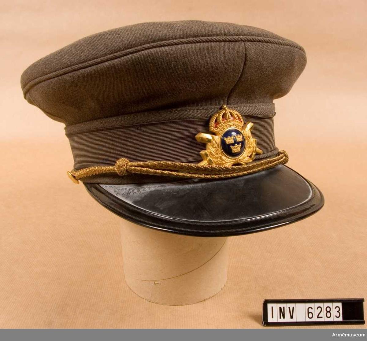 Storlek: 57. Tillverkad av gråbrungrönt yllediagonaltyg med svart skärm, undertill grön, grått mössband i rips, mössmärke m/1952 förgyllt och med blå knapp, mössträns av flätad guldtråd. Mössan invändigt märkt.