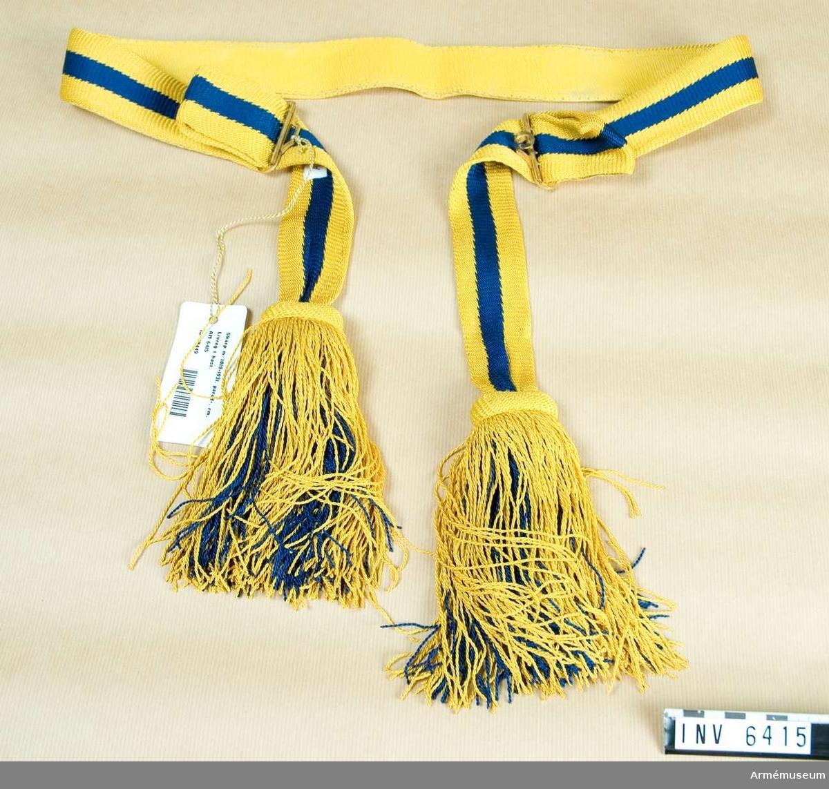 Av s k virkat gult/blått silke m tofsar. Längden regleras m två spännen som även tjänar till hophäktning. Bäres m tofsarna på vänster sida.