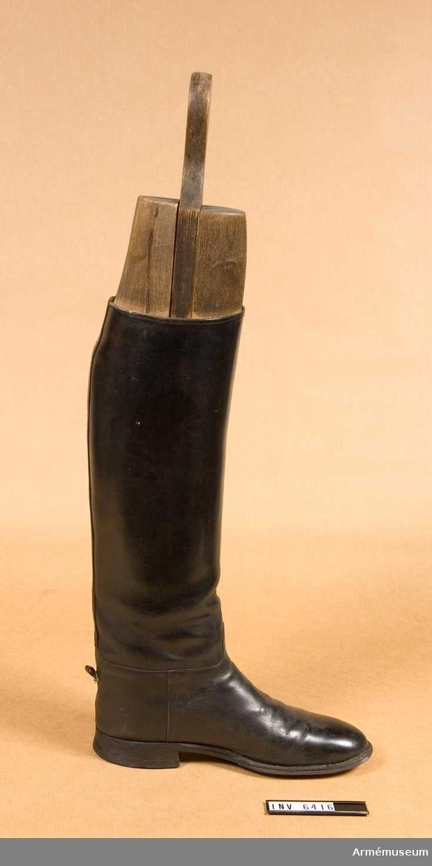 """Storlek 42. Av svart lackläder. Bäres utanpå ridbyxorna vid parad. Skaften når till knävecken. Gummiklacken är märkt """"Good Year"""". Med tillhörande stövelblock i tre delar."""