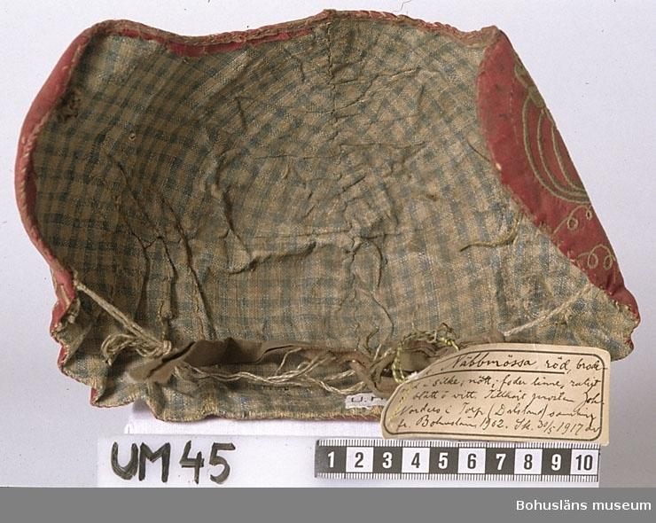 Mössan har styv stomme av papp, dock ganska tunn och sladdrig. Yttertyg av rött siden. Enligt text från 1917 i gåvobok purpurfärgad. Fodertyg av smårutigt linne i blått och vitt (gulnat, mörknat).  Rester av ljusrött sidenband längs nederkanten. Broderi i tambursöm med silke. Ett stiliserat mönster med blommor, blad, linjer och cirklar. Mönstret finns framtill och på sidoflikarna. Inget mönster mitt på kullen och bak. Färgerna i broderiet är vitt, mycket ljust blågrönt och ljusgult. Fem veck i varje sida bak. Vecken är svängda upptill. En tvinnad lintråd som troligen varit dragband, hänger på insidan av mössan. Den är fastsydd i fodret vid de yttersta vecken. Det är hål mellan foder och yttertyg nära där lintråden är fastsydd, så förmodligen har den suttit inuti från början. Nu fungerar den inte längre som dragband, därför har vecken släppt. En stickning 1,3 cm från nederkanten längs framkant och sidor. Ingen kanal för dragband. Stumpar av en remsa av brunt småmönstrat bomullstyg finns invändigt på sidoflikarna, fastsydda i fodret. En remsa av samma tyg är fastknuten vid det som troligen varit dragband. Vid det är även en gammal etikett fastknuten, med blågult snöre. Sliten, speciellt upptill vid vecken på höger sida. Tråden i broderiet är bortsliten på en del ställen. Mycket smutsig. Stor brunsvart fläck uppe på kullen och mindre fläckar bak. Fodret mycket smutsigt. Mössans form är deformerad eftersom pappstommen inuti är skadad, sidoflikarna är böjda och det är veck på kullen. Tillverknings- och användningstid osäker. Dateringen till 1700-tal är gjord utifrån att mössan är ganska stor och går ner i en flik i pannan samt att den fått samma sakord (näbbmössa) vid första katalogiseringen  som en annan mössa som troligen är från 1700-talet.  Enligt text i gåvobok (diarienummer D:4B:1) är mössan från Bohuslän men inköpt av fru Rosa Jacobowsky 1904? på auktion efter fornsaks samlaren Johan Norder i Torp socken Dalsland.  Rosa Jacobowsky (1860-1954), gift med grosshandla