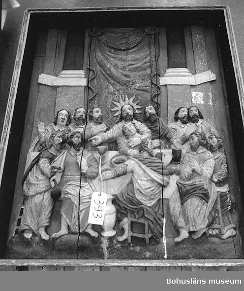 Altaruppsats från 1675, rikt skuren i trä med central skulpturscen, krön, sidostycken, pelare och kapitäl som krederats och målats med mager oljefärg samt förgyllts med oljeförgyllning. Förgyllningen uppvisar både bladguld, slagmetall och förmodligen silver, som mörknat påtagligt. Tillhörande skulpturer överst på ömse sidor om kröndekoren; UM394, UM395.  Centralmotivet skildrar nattvardens instiftande i en skulpturscen. Över scenen läses nattvardens instiftelseord på danska. Under skultpruscenen inskriften:  ANNO 1671 ER DENNE KIERKEBYGNING I JESU NAFN BEGYNT OCH UNDER PASTORIS JOANNIS COLSTRIPII FLID MEDH SIT INREDE ANNO 1675 FULBORDET MEDH MIDDEL FRA EGNE RINGE INTRADER, ANDRE GOT FOLCKIS TILHJELP OCH FORNEMMELIG H. KONGL. MAJIT:S WOR ALLERNADIGSTE KONUNG CAROLI XI TILGAWE AFF 150 RIXDALER.  Altartavlan komer från Norra Ryrs kyrka, riven 1873 och benämnd Norra Ryrs kyrka fram till år 1884, idag Lane-Ryrs kyrka.  UM384, UM 385, UM389a-i, UM393a-i, UM394, UM395a-b, UM401, UM404a-b, UM405a-g, UM5660:1-57 samt UM65.1.1 är samtliga inventarier från den gamla kyrkan.  Beskrivning av altaruppsatsens delar: a. Tavla med nattvardsframställning; h. 120, br. 104 cm b. Överdel; l. 224 cm c. Krön till överdel; br. 132, h. 58 cm d. Pelare; h. med platta över kapitälet 113 cm e. Pelare, som föregående h. 113 cm f. Sidostycke; i 2 delar I-II, h. med tappar 128, br. 67 cm g. Sidostycke; i 2 delar I-II, h. med tappar 131, br. 69,5 cm h. Underdel; l. 201 cm i. En lös del, tillhörande UM393h  Altaruppsatsen ska enl. uppgift i artikel i Bohusläningen den 30 april 1963 vara skänkt till församlingen av Karl XI som ett led i försvenskningen av Bohuslän.  Ytterligare foto i Uddevalla museums kyrkliga utställning år 1920, se UMFA53292:0013, UMFA53710:0075.  Ur Nationalencyklopedin, NE.se: Altarprydnad Under 1500-talet utbildades i Italien en ny typ: en central målning eller skulptur, omgiven av en rik, klassiserande omramning. I den tyska renässansen utvecklades altarprydnaderna till altar