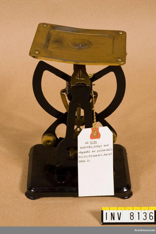 """Brevvåg tillverkad av plåt. Väger föremål vägande upp till 500 gram. Två skalor, dels en med 10, 20, 30, 40, 50, 60, 70, 80, 80, 100 g, dels en med 100 50 200 50 300 50 400 500 g. Märkt i en taggig ram """"M"""" och """"Orginal Columbus BILATERAL"""". I botten en bokstav """"C"""" av vit oljefärg. Ingår i fotomaterielsats 7 låda 2."""