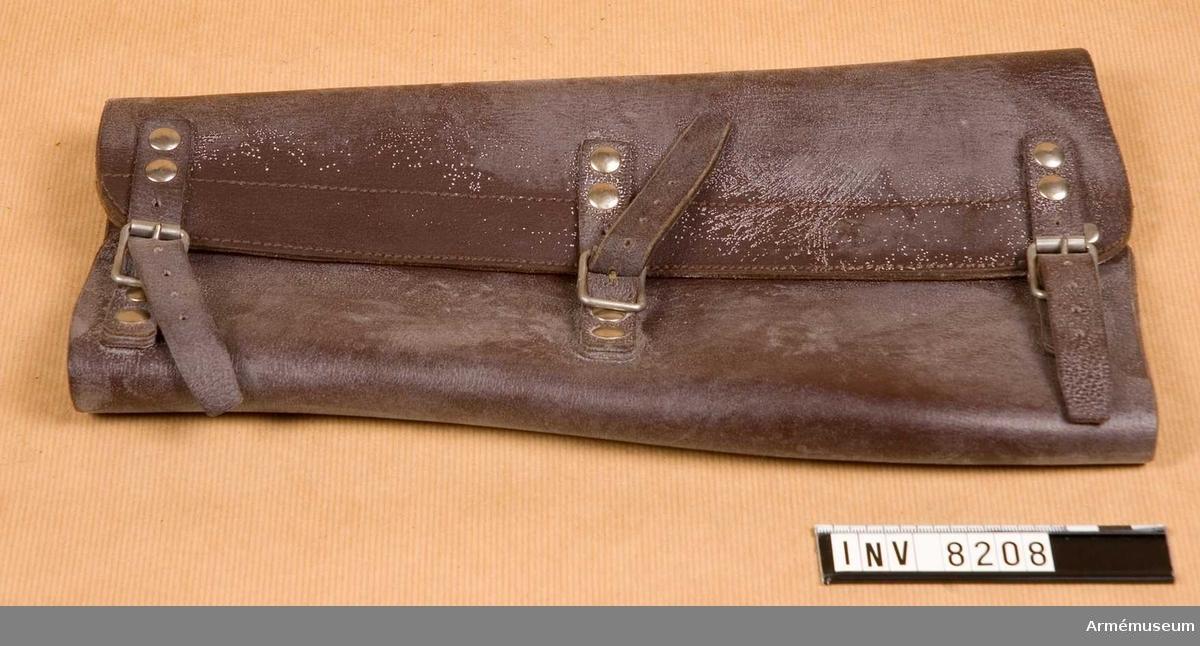 Av brunt läder med på yttersidan tre remmar att knäppas mot vita (vitmetall) spännen. Vidd nedtill 320 mm, upptill 420 mm. Nyskick 111.