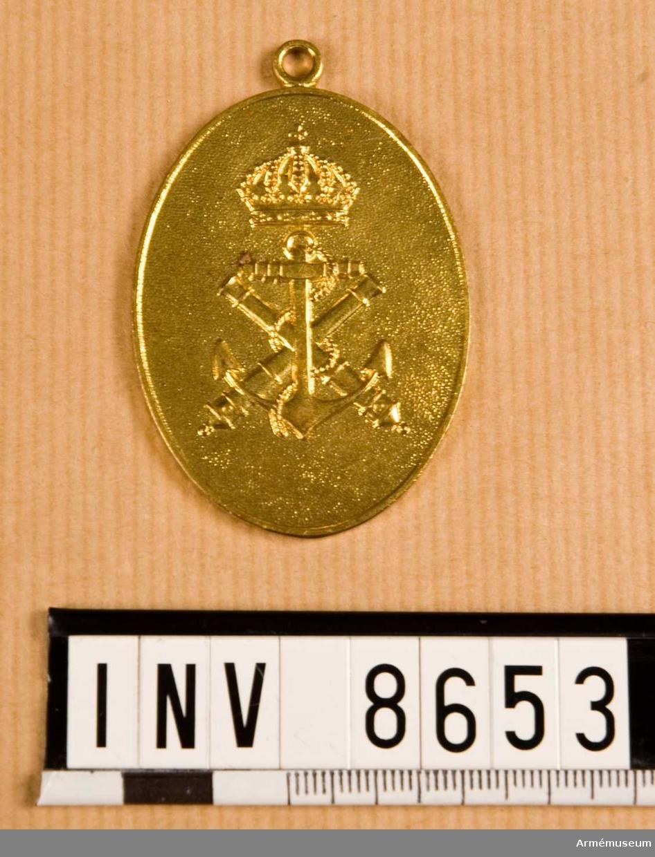 Höjd 55 mm. Bredd 40 mm. Vikt 27,7 g. Förgyllt ovalt märke med kustartilleriets emblem under kunglig krona. På frånsidan står i den övre kanten ORDNINGSBEFÄL och i den undre kanten MARINEN. Mitt på står det KFL 10. Upptill finns en ring.