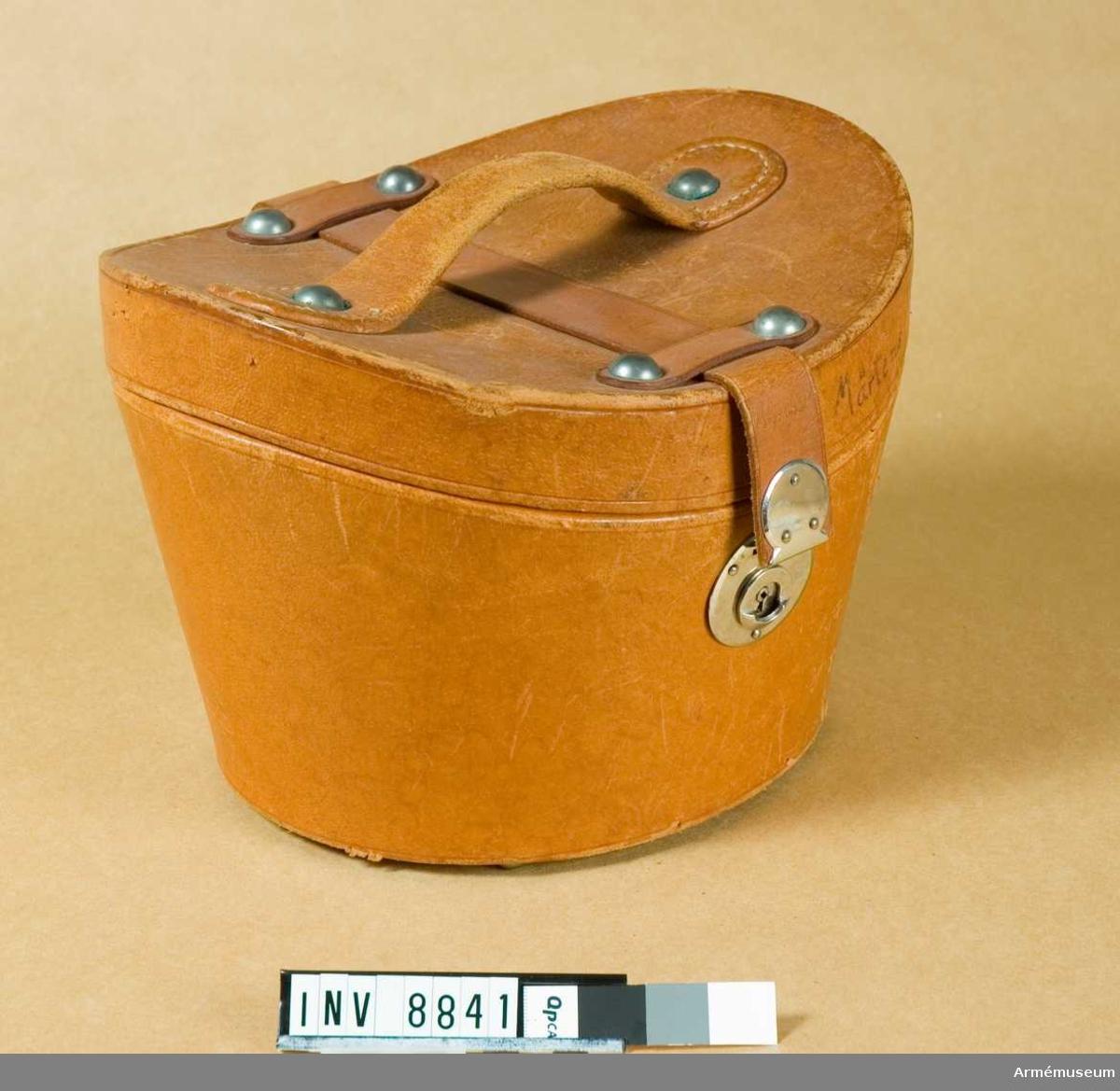 Höjd fram 160 mm. Höjd bak 160 mm. Höjd sida 190 mm.Av brunt läder formad för käppin med konkavt lock med handtag och rem som går att låsa på framsidan. Locket märkt  Mårtens A 3.