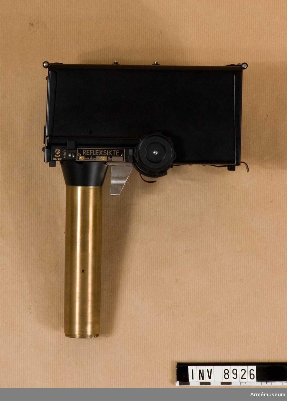 Kaliber 40 mm. Märkt: AGA Baltic 41707. Reflexsikte 40 mm. automatkanon m/36 Nr:.Bestående av: 1 st reflexsikte, 1 st förvaringslåda av trä, mått 370 x 145 x 230 mm, vikt 4250 g, 1 st reflexglas,  1 st lampa,  1 st flanelltrasa för torknng av glasen.   Tillverkningsnr 41707