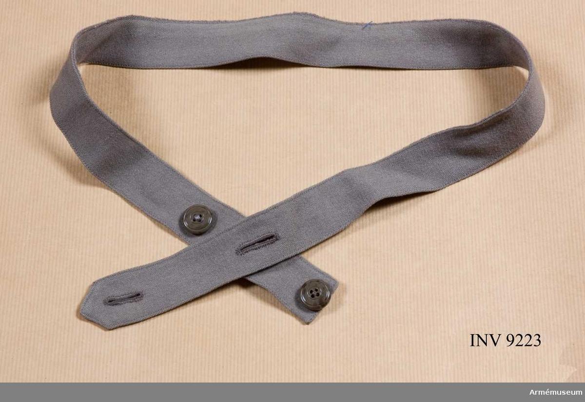 Skärp t klänning m/1931, SLK. Av grått ylletyg med knäppning med två knappar. Tillhör s k föreningsdräkt.