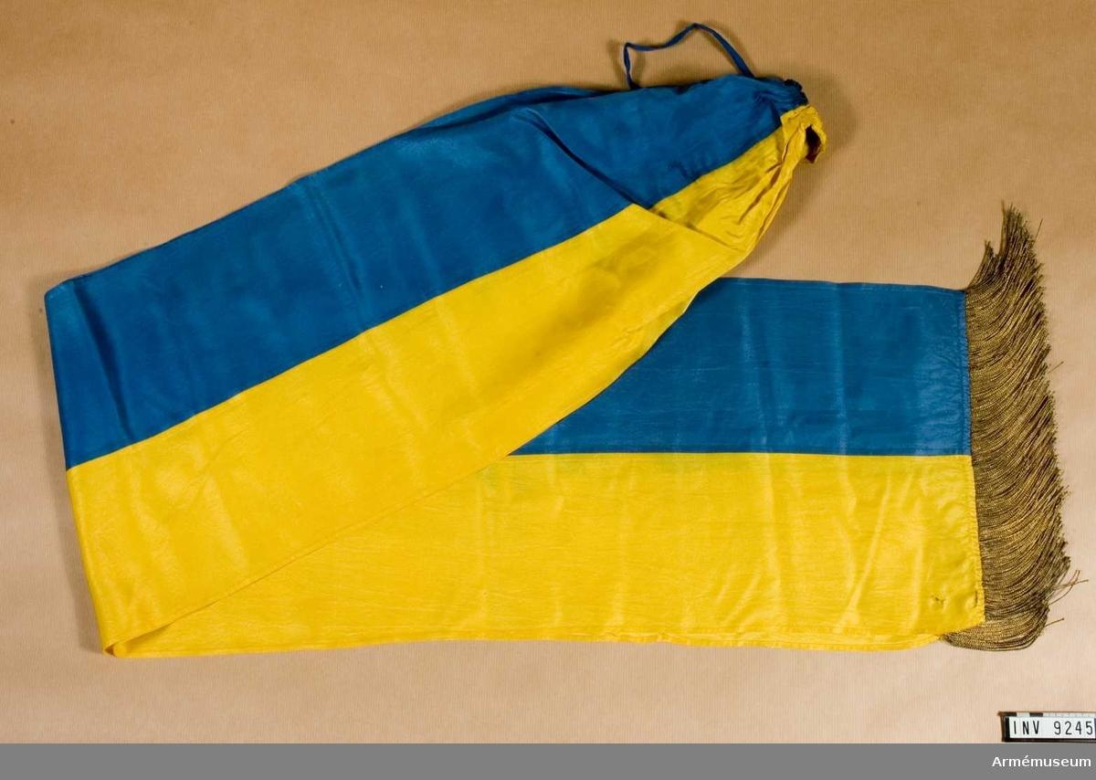 Sydd för hand av hälften blått och hälften gult siden. Kortsidorna är försedda med en enkel guldfrans.