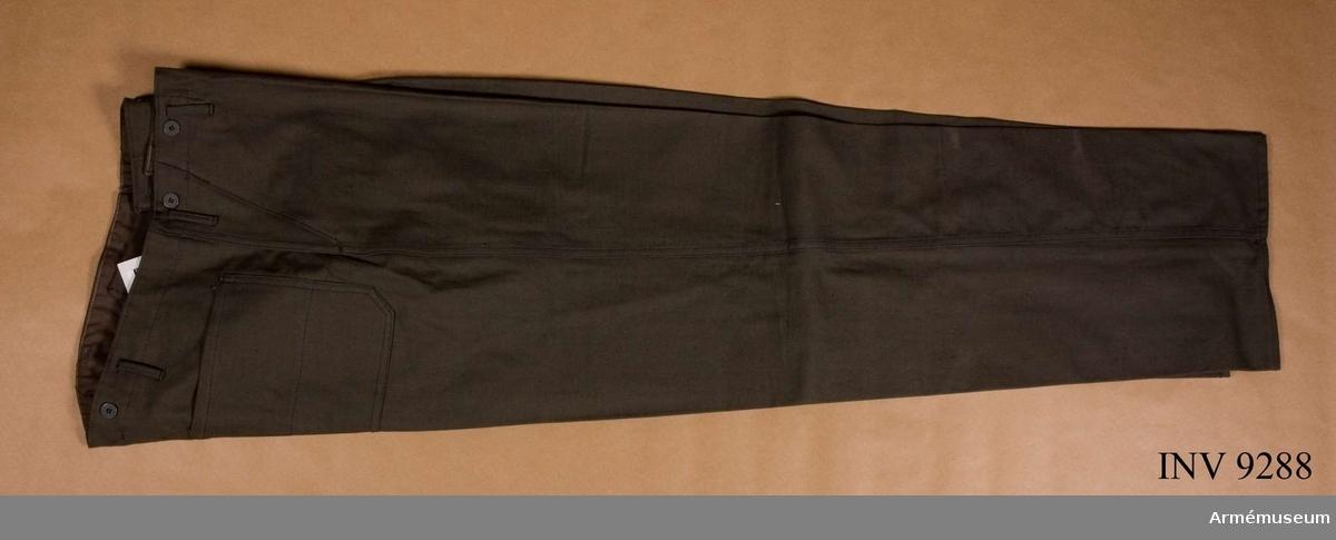 """Överdragsbyxor m/1940, grå. Sydd av grå bomullstwills, en kypertvara. Gylfknäppta och med knappar i midjan för hängslen. Hällor för livrem. Två snedfickor i sidan och en bakficka. Stämplade på insidan med """"tre kronor"""" DY 112."""