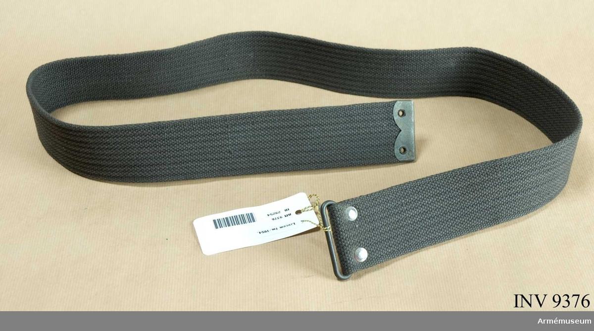 Av gråsvart bomullsmaterial, cord. Har beteckningen svart. Metallbeslag i de båda ändarna.