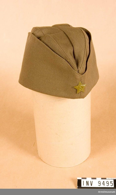Röda armén.Sommarfältmössa i tunn yllediagonal med uppvikta brätten med en grönmålad stjärna mitt fram. Svettrem av grå galon och foder av grönt bomullstyg. En tryckt stämpel på vänster foderhalva i ryskt skrift och med angivelse av storlek II.Gåva från Sovjetiska arméns centralmuseum.