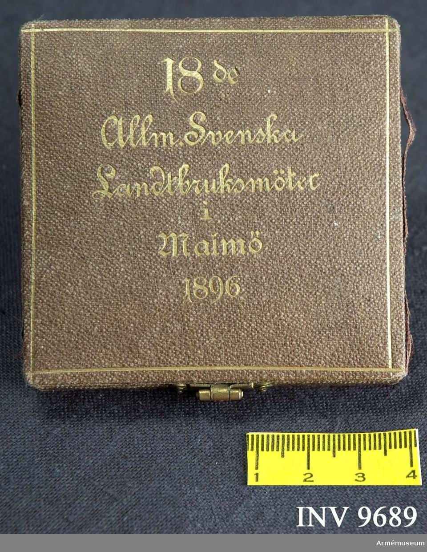 Samhörande nr är 9688-9689. Ask till minnesmedalj, allmänna svenska landbruksmötet i Malmö 1896. Tillverkad av ursprungligen oxblodfärgat klot med guldtext enligt följande: 18de Allm. Svenska Landtbruksmötet i Malmö 1896.Invändigt är asken klädd med röd sammet och har ett urtag för medaljen. Asken knäpps med ett gulmetallspänne. På sidorna av locket har det påklistrade materialet släppt något. Botten är märkt: A. Svanboms bokbinderi.Minnesmedaljen förvaras i asken.