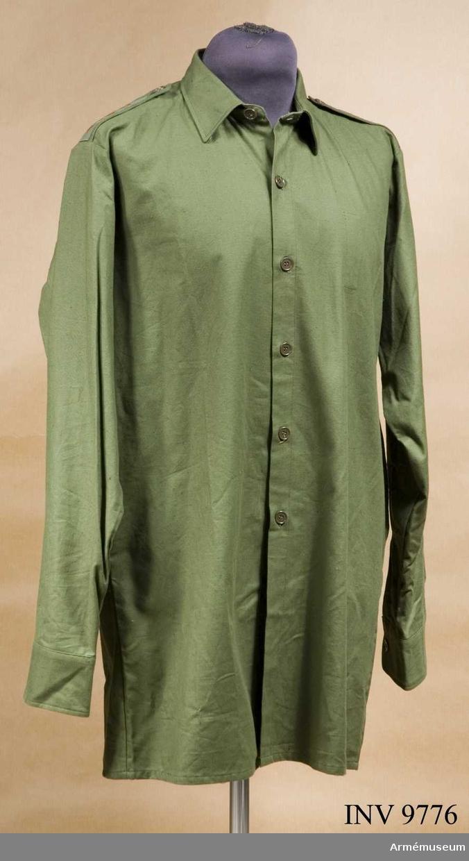 Skjorta fm/1968. Storlek 39. Av grönt bomullstyg, har fast krage,fasta axelklaffar påsydda gradbeteckningar saknar bröstfickor. Ärmar med fasta manschetter.