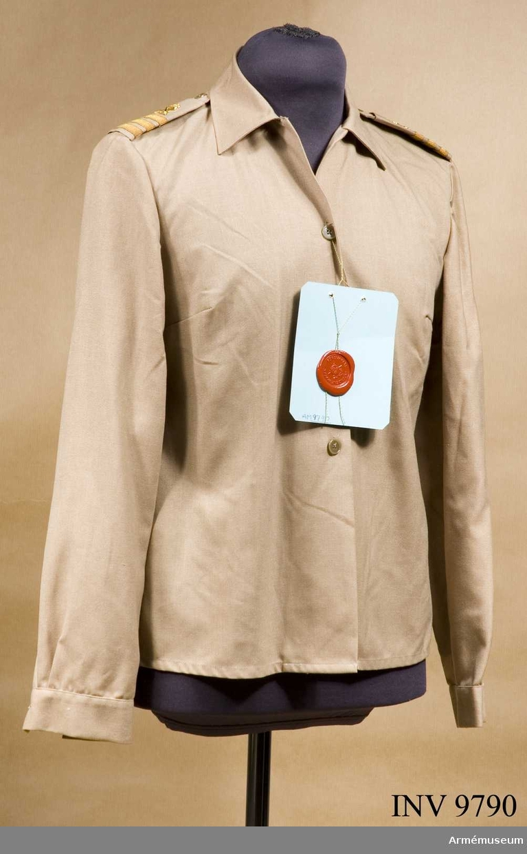 Blus m/1969, ur tropikuniform för kvinnlig FN-personal. Storlek 38.  Fastställd 1969-09-19. Knäppt mitt fram och har krage och manchetter. Fasta axelklaffar med hylsa för gradbeteckning.