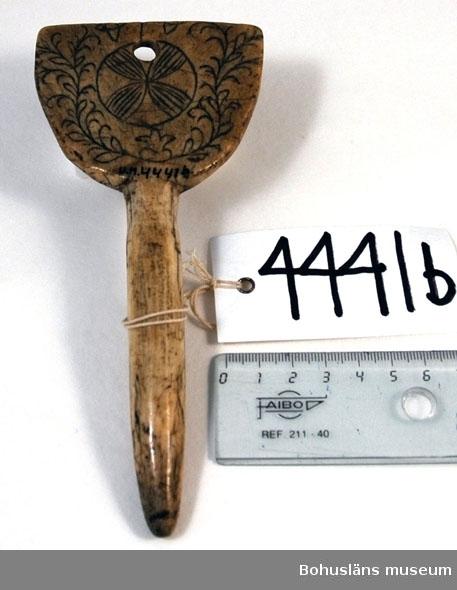 Rund pinne med triangulär platta upptill. På en av sidorna finns ristad och svärtad dekor bestående av ringar och uddsnittslinjer. Baksidan har mörknat på grund av användning. Enligt Stig Harry Johansson, Tärnaby som besökte museet 17/3 1988 är föremålet tillverkat av horn från älg eller ren. Kan vara av äldre datum.  Rosa Jacobowsky (1860-1954), gift med grosshandlare Efraim Jacobowsky, Uddevalla.  Litt.; Nylén, Anna-Maja, Hemslöjd, Håkan Ohlssons förlag, Lund, 1978, s. 396-401.  Ur handskrivna katalogen 1957-1958: Två selpinnar av ben a) Mått: 16,5 x 9 cm; till formen en trekant f. platta m. skaft; å ena sidan skuren dekor m. ringar, sicksacklinjer m.m. Hel.   Svar på förfrågan kring föremålen UM003945, UM004440, UM004441, UM004442 till Ajttemuseet, Jokkmokk januari 2007, som skriver: Vi uppfattar inte föremålen som direkt samiska, inte heller i gravyren. Visst har det funnits bofasta samer, så det kan vara möjligt, men ofta hade de också renar för transport.   Lappkatalog: 40