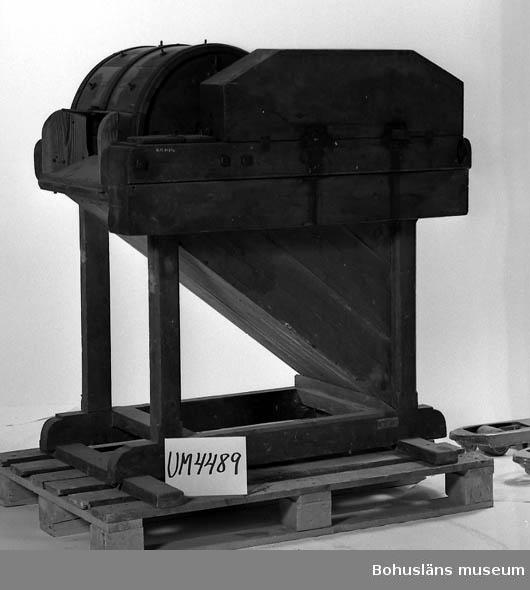 Ur handskrivna katalogen 1957-1958: Tröskmaskin L. 108; Br. 61,5; H. 146 cm ; handdriven. b och d = 2 vevar av järn, m. trähandtag; L. 42,5 cm; b och c) d. ena, b), har en bult att spänna fast med. d) Huv över kugghjulen av trä, mått: 76,5 x 24 x 13,5.  Lappkatalog: 51