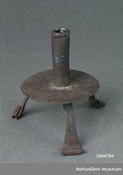 """Ljusstake av okänt ursprung och ålder. Modellen går tillbaka till 1600-talet och kan ha tillverkats in på 1800-talet. Ljusstaken användes som förebild vid nytillverkning av ljusstakar till Museikaféet år 2000. Dessa gjordes av konstsmed Inge Dahlgren, som då hade sin smedja i ett ombyggt brygghus i Västra Tunhems prästgård vid foten av Hunneberg. Ljusstakarna är stämplade """"ID"""" på ett av de tre benen.  Ur handskrivna katalogen 1957-1958: Ljusstake av järn på 3  ben H: 14,5. Föremålet helt. Rostad.  Lappkatalog: 90"""