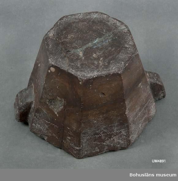 Åttakantig mortel med två handdtag. Allt formad ur ett stycke. Ristad dekor i form av en bård på utsidans övre del. Även ristning på överkanten. Ristad yta halvvägs ner på insidan. Den har varit sönder i fyra delar som sammanfogats.  Ur handskrivna katalogen 1957-1958: Mortel m. stöt 8-kantig mortel med stöt av röd sten. Något skadad. Diam: 18,5. (yttermått)  Lappkatalog: 64