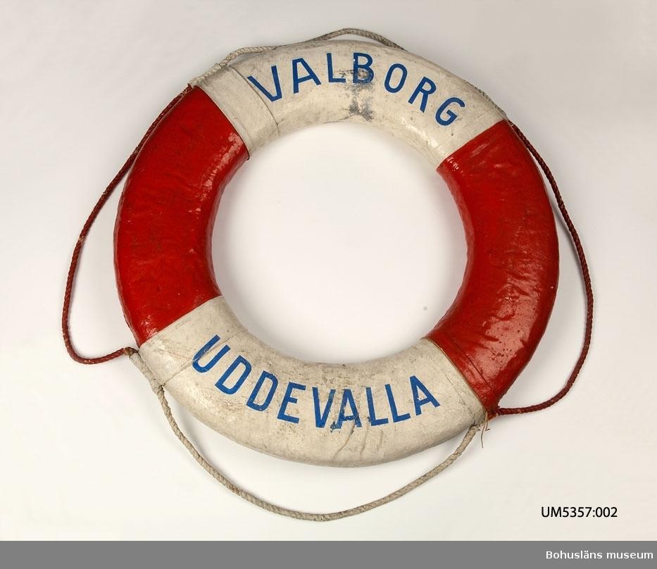 """Livboj med texten SS Valborg. En av tre livbojar som tillhört Ångfartygs AB Bohuslänska Kusten och köptes in till Uddevalla museum i samband med företagets auktion 1950.  Valborg byggdes på Götaverken 1874 för William Thorburns Söner, Uddevalla och trafikerade linjen Göteborg-Uddevalla-Lysekil och såldes 1876 till Ångfartygs AB Bohuslänska Kusten.  1950 såldes ångaren till Gunnar Jansson, Uddevalla. Valborg byggdes om till pråm för Uddevallavarvet och såldes för skrotning 1957. Se fotografi UMFA54477:0217  Ångfartygs AB Bohuslänska Kusten var ett av de rederier som revolutionerade kustens gods- och passagerartrafiken under 1800-talet. Rederiet startades under namnet """"Ångbåtsaktiebolaget Bohusländska Kusten"""" år 1876. Rederiets fartyg, huvudsakligen ångfartyg, användes för passagerartrafik men även för frakt av gods till de olika orter som låg på öarna där ångbåtsbryggor fanns. Plötsligt blev skärgården tillgänglig för alla. Kustbornas kontakter med fastlandet ökade. Det blev enklare och säkrare att resa. Restiderna blev kortare och gick för första gången att beräkna. Oberoende av förlig vind blev ångbåtarna snabba och tillförlitliga fraktfartyg. Beroendet av väder och sjögång minskade. AB Bohuslänska Kusten gick i konkurs i slutet av 1950-talet i takt med att transport och kommunikation till lands tog över.  Ur handskrivna katalogen 1957-1958: Tre livbojar, S/S Borgila, S/S Valborg, S/S Uddevalla def. Yttre diam: 80-73. Vit och rödmålade. Föremålen hela.  Livbojarna hade tidigare samma inventarienummer."""