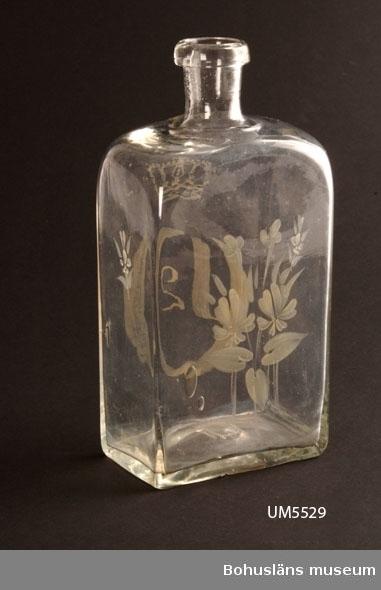 Slät fyrsidig karraff för brännvin i färglöst glas. Kort hals med påklippt halsring, regalin. Svagt stucken botten (uppåtstående) med rått puntelmärke.  Målad dekor i vitt med på ena bredsidan Oscar II:s krönta monogram och på andra en blomsterdekor. På flaskans sidor en liten blomsterdekor. Propp saknas. Luftbubblor.   Oscar II, svensk kung 1872 - 1907, (i Norge till 1905)  Ur handskrivna katalogen 1957-1958: Glaskaraffin Bottenmått: 9,8 x 6,2 H. 20,5. Fyrsidig brännvinsflaska. Obetydligt skadad i botten. Märkt (12). Propp saknas.  Lappkatalog: 61  Litt: Hermelin, C. F., Welander, E.: Glasboken. Historia, teknik och form. Askild & Kärnekull 1980. Lersjö, G.: Gammalt glas. ICA bokförlag 2005. Nisbeth, Å. Glas i Sverige intill 1900. Ur Svenskt glas. Wahlström & Widstrand 1991. Steenberg, E.: Flaskor och glas. Nordiska museet 1952. Steenberg, E.: Svenskt glas. Bohusläningens AB Uddevalla 1964.