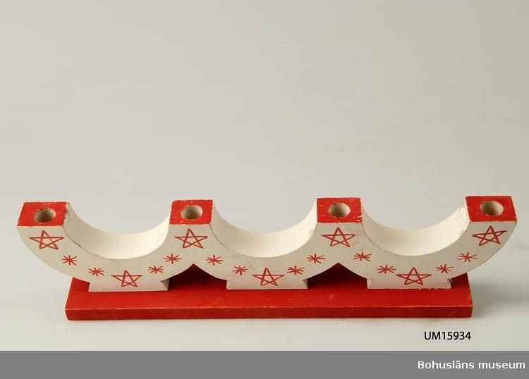 Utsågad, tre bågar med plats för fyra ljus. Vitmålad med röda stjärnor.  Placerad på röd bottenplatta.  Se UM015810