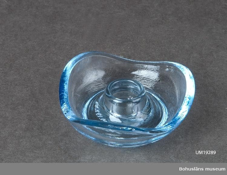 Liten ljusstake i ljusblått transparant glas. Kommer från insamling av föremål från vindskontor Antonssons Livs m.fl. Kvarteret Ridhuset, Södra Drottninggatan 12, Uddevalla (rivningsobjekt).