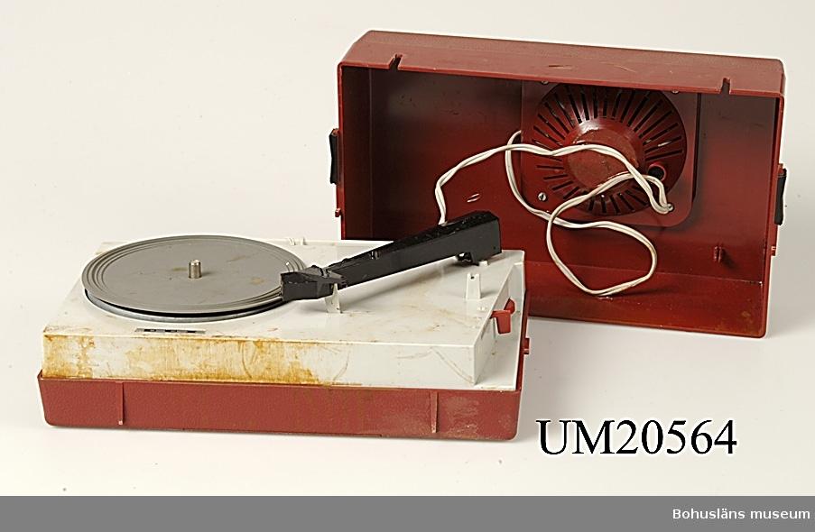 Batteridriven grammofon med högtalare ihopsättbara till bärbar enhet. Röd och grå plast. De röda plastdelarna har ett lågmält präglat mönster i relief. Handtaget är grått.  Ett föremål som på 1960-talet hade stor attraktionskraft bland tonåringar.