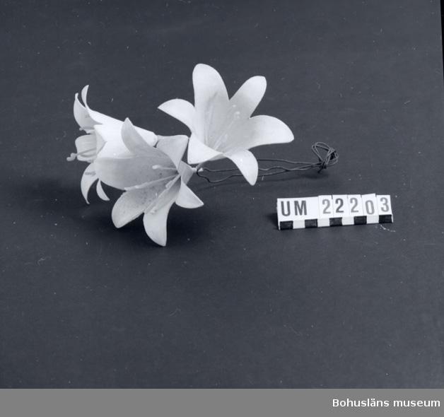 594 Landskap BOHUSLÄN  Vita liljor med gula pistiller och ståndare tillverkade av plast; stjälkar av järntråd.  UMFF 89:2