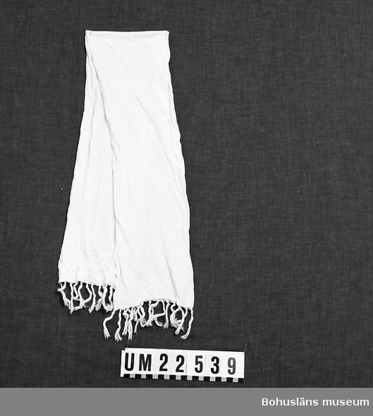594 Landskap BOHUSLÄN  Rundvävd i vit trikå, fransar i ändarna.  UMFF 123:9