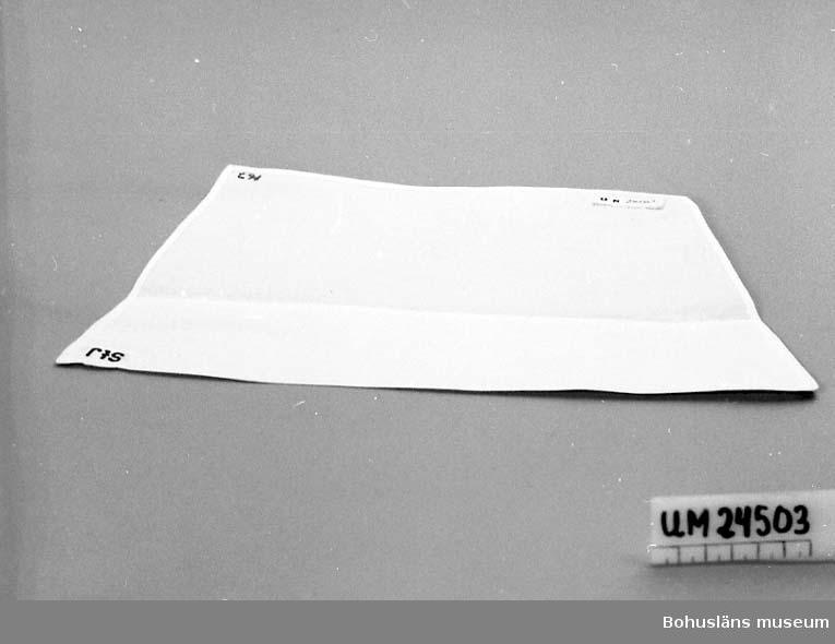 """594 Landskap BOHUSLÄN  Vit fållad tygbit. Fyrkantig. Den ena långsidan är kortare än den andra (10 cm).  I ena hörnet finns en märklapp med ceris text: """"StJ"""". I ett annat hörn står: """"167"""" broderat."""