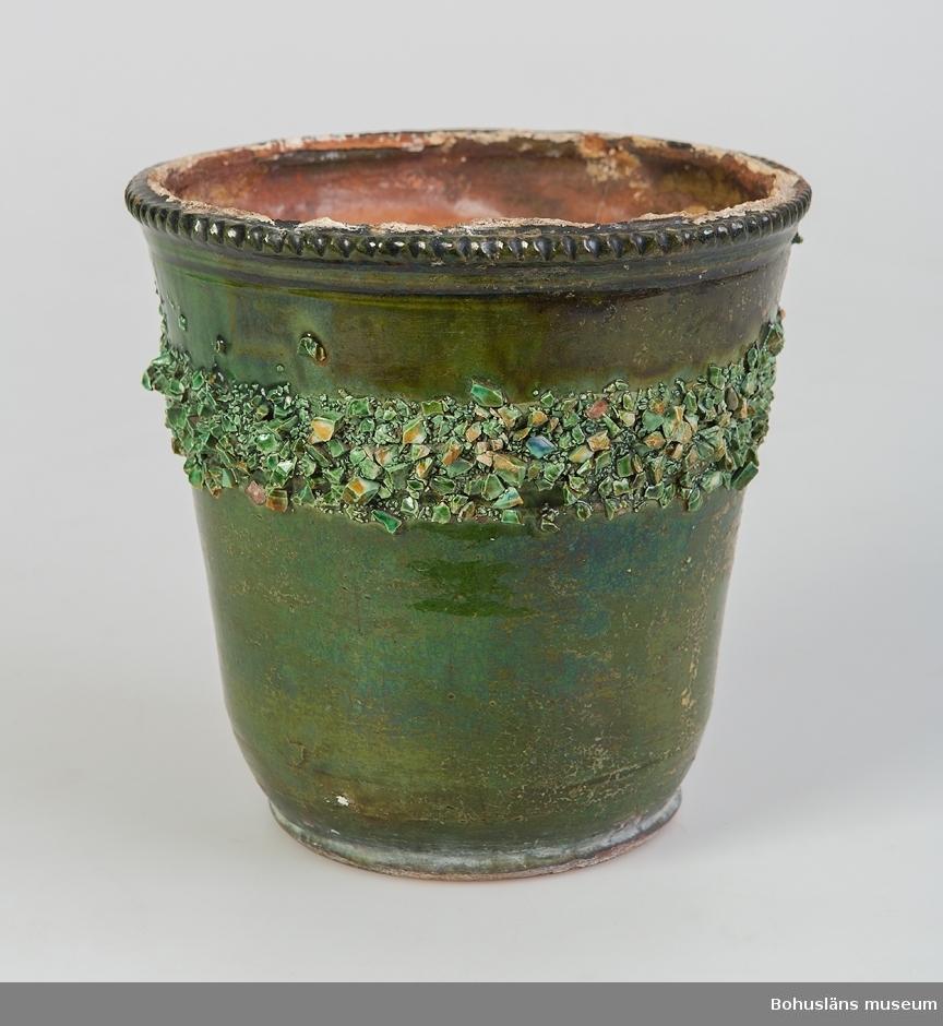 """Konisk öppen form. Drejat rödgods med bearbetat vågigt mönster upptill på utsidan av kanten, hål för vattenavrinning i botten, grön glasyr, dekor/bård av chamotte runtom ca 1/3 ner på sidan, 3 cm bred. Chamotten består förmodligen av tätsintrad krossad keramik. Oglaserad inuti. Skador pga användning.  Krukan kan härstamma från krukmakarsläkten Hjoberg som haft krukmakeri i Västra Bodane, Frändefors socken under stora delar av 1800- och 1900-talen.  Litteratur: Hembygden, Dalsland 1973, """"Pottkakelugnen"""", om krukmakarsläkten Hjobergs kakelugnstillverkning, av Christer Järlgren, s. 25-58;  """"Krukmakare och kakelugnsmakare"""", Tom Möller, Raster förlag (1999), s. 22-27. Bilagepärm under UM18181: Informationsblad """"Välkommen till Hjoberg krukmakare på Dal"""" (2000-talets början) samt """"Hjobergs krukmakeri"""" (1997)."""