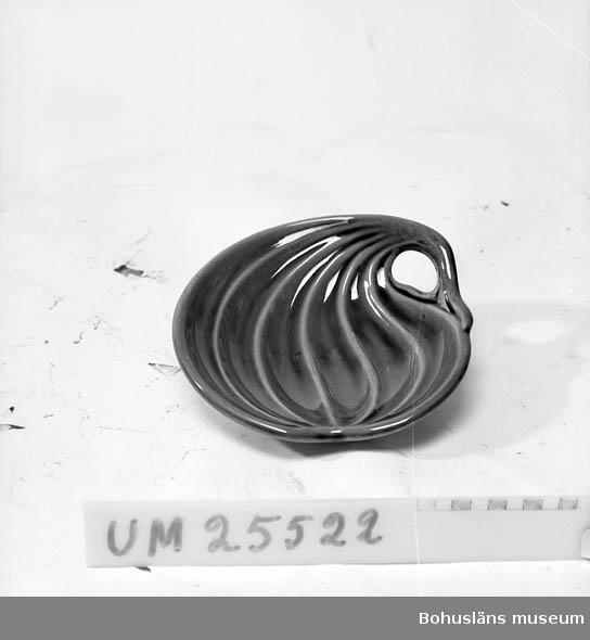 """Svagt asymmetriskt , närmast runt fat, format del av sfär. Asymmetriskt formade åsar går över ovansidan. Vid ena sidan ett hål.  På undersidan märkt med svart stämpelsignatur: """"SYCO Sweden 817-gk."""" Samtidigt förvärvad som UM25521."""
