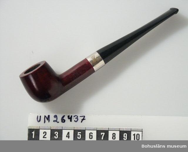 """Föremålet visas i basutställningen Uddevalla genom tiderna, Bohusläns museum, Uddevalla. Slätt piphuvud av björk infärgat i mörkt brun-rött. På piphuvudets skaft står det: """"TED INRÖKT PAT."""" På skaftet sitter ett rakt munstycke troligen gjort av bakelit. Inte brukad. Mellan skaft och munstycke sitter en metallring märkt: """"SKAPI"""". Ovanför texten är en krona avbildad."""