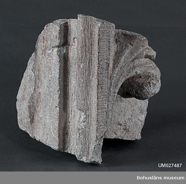 Mångformig byggnadsdel av täljsten, skulpterad med volut och kolonnsida. Toligen del av fönster eller dörröppning.     Se även UM029202:0031