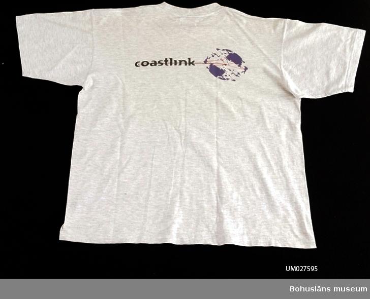 """T-shirt för """"Coast-Link-projektet"""" . Gråmelerad T-shirt i herrstorlek XL med kort ärm.  På bröstet ett påtryck med texten: coastlink i svart www.coastlink.nu i rött. På ryggen påtryck med texten: coastlink och en bild på jordklotet med röda streck mellan olika platser. I nacken märkt med vävd etikett md texten: TeeRex  KING OF COTTON Ganska fläckig.   Till T-shirten hör ett informationsblad"""