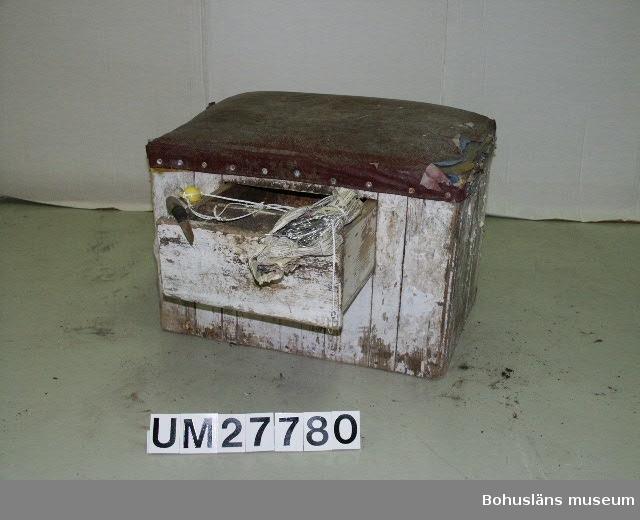 """Föremålet UM027780:1 (pall/trälåda) visas i basutställningen Kustland, Bohusläns museum, Uddevalla.  Rektangulär, tung trälåda, spikad av enkla, stående, spåntade brädor. Vitmålad med stoppad sits klädd med påspikad, vinröd galon, spänd över ett tidigare skydd av blå canvas.  Utefter långsidan, under sitsen finns en utdragbar, kraftig låda. I denna ligger en kniv, UM027780:2. Väl slipat knivblad med skaft av trä, förstärkt med svart isolertejp. I lådan förvaras också  två ombundnda omgångar  med förberedda extra krok, den ena känsor med krok och flöten, den andra utan flöten UM027780:3, jfr. uppgifter under UM027777.  Man satt på lådan och satte fast nya kortmottar och agnade på backan krokar. Agnet, kniven och kortmotten förvarades i den utdragbara lådan i pallen. Till agn användes vanligen makrill, men också  lubb, sill eller bläckfisk.  Agnet  togs upp ur frysen till lådan efterhand som det användes.  Det är en iskall hantering. Varje makrill skars i 8 bitar - 4 på varje halva.   Varje man hade sin egen agnepall där man satt och rensade makrill och agnade på backorna.  Pallen var personlig egendom och togs med när man mönstrade av efter avslutat fiske. Det kunde hända att någon kille - då man var på hemväg - kastade pallen överbord och sa  """"- Aldrig mer"""". Men nästa säsong satt han där igen, på en ny pall.  Pallen och övrigt material är insamlade från Klas Berntsson i Grundsund och är använt på långafiske ombord på LL Sandö 158 under åren 1972 - 1992. För ytterligare upplysningar om förvärvet, se UM027777."""