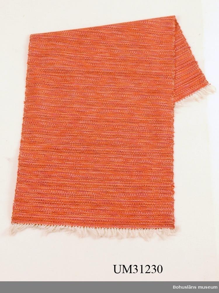 Maskinvävd rödmelerad plastmatta; flera olika röda plastband har använts som inslag. Knuten frans i båda ändar.