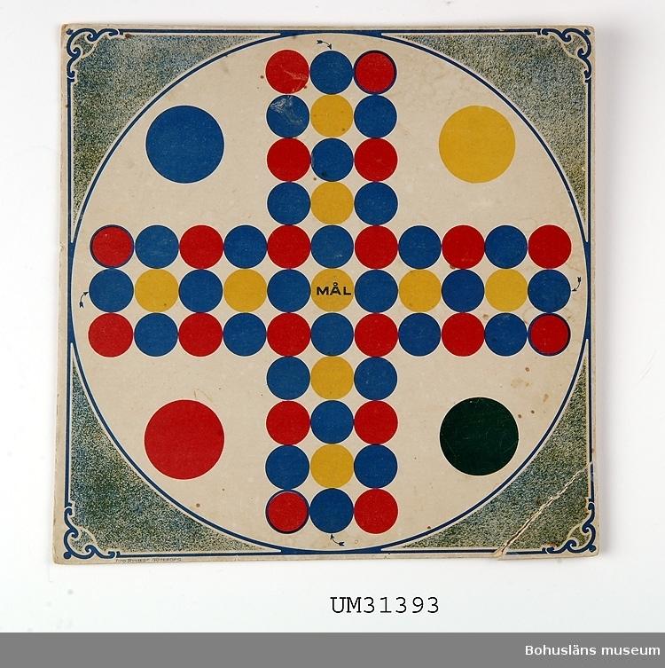 """Ett Fia-spel med spelpjäser. Kartong med tryck på ena sidan.  Spelplan med blå,  gula och röda rundlar, i mitten med texten """"MÅL"""". Nere till vänster tryckt LITO RYSTEDT GÖTEBORG På basidan märkt med blyert: Abrahamson.  Föremålet har använts av familjen Abrahamson i deras sommarstuga i Sundsandvik, byggd 1939. För ytterligare upplysningar om förvärvet, se UM031385."""