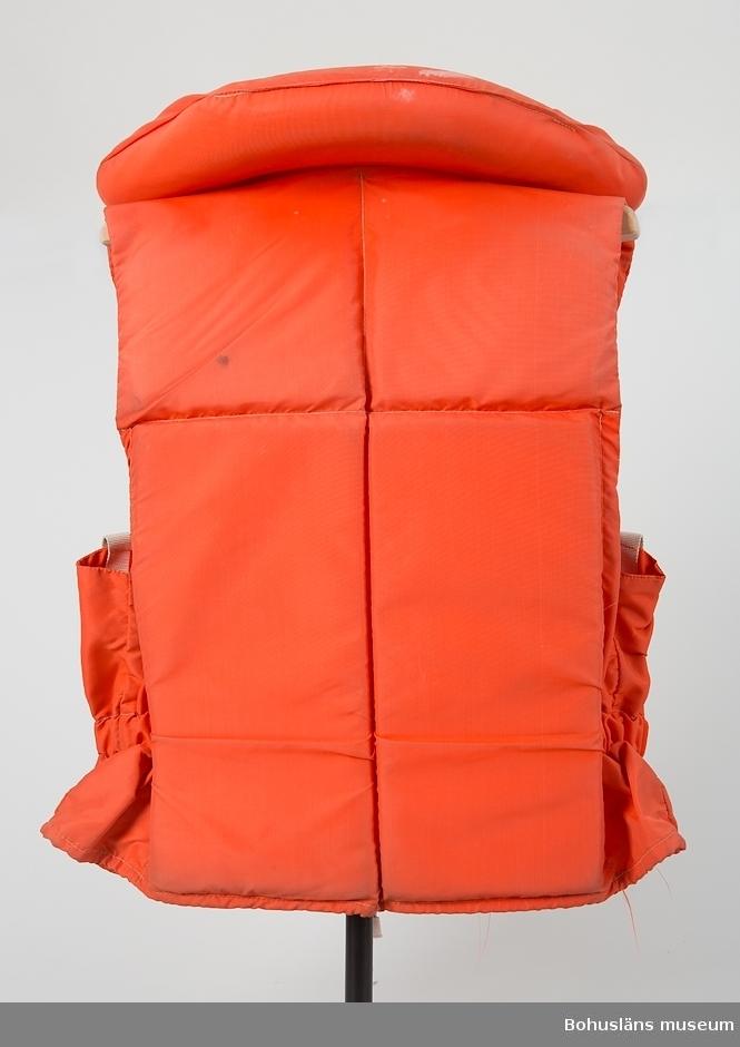 Flytväst av orange nylontyg med ilagda flytmaterial fram- och baktill samt i smal, rundad krage. I sidan resår. Knäpps med två plastknäppen på framsidan, fästade mot vita förstärkningar av plastväv.  Nylonsnöre för stängning i halsen och längs hela nederkanten. Ficka för visselpipa med texten MÅSEN 3001. Tillhörande visselpipa i orange plast, fästad i nylonsnöre. Två vita reflexband på framsidan.  På insidan tryckt text:  VDN Seglarväst tillv. 1974/75 För vuxna simkunniga Förväxla ej seglarvästen med den  säkrare räddningsvästen. Se efter att västen är oskadad. Provbada minst en gång om året och kontrollera att västen fungerar.