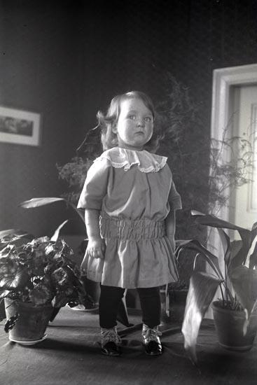Margit Lysén porträtterad stående på ett bord bland gröna växter