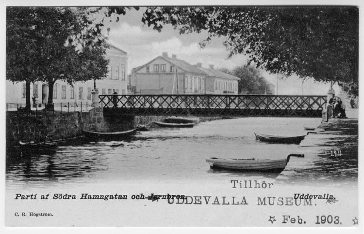 """Tryckt text på vykortets framsida: """"Parti af Södra Hamngatan och Järnbron Uddevalla."""""""