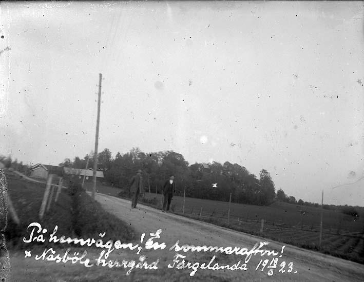 """""""På hemvägen! En sommarafton! Näsböle herrgård Färgelanda 18/6 1923"""" Två män i kostym och hatt går längs en väg genom ett jordbrukslandskap"""