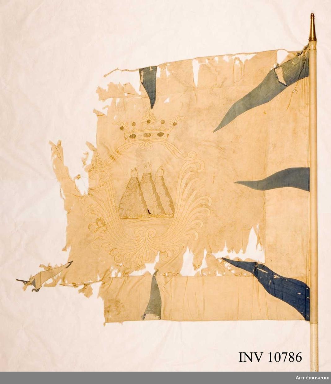 Grupp B I.  Duk av vitt fyrskaftat, fansiden (kypert) med från hörn och sidornas mitt, inåtgående, åtta st flammor av blått taft. I mitten broderat: Västmanlands sköldemärke tre eldsprutande berg (milor) med gula flammor omgivna av en sköld bildad av stiliserande palmkvistar och krönt av en öppen krona. Skölden och kronan i plattsöm av gult silke, den senare med pärlor i silver och stenar i rött och blått silke. Bergen i schattersöm i grå och bruna silken flammor av gula silken. Kantad med  silkesnöre. Duken kantad med silkesnodd och fäst med förgyllda spikar på sidenband vitt.Stång av furu, vitmålad. Doppsko av mässing. Spets av förgylld mässing. Bladet med Carl XIV (Johans) krönta namnchiffer inom ram av palmkvistar, krönt av en strålande sol. Holken 120 mm, bladet 167 mm långa. Fodralet av grov lärft och brunfärgad, längd 1730 mm.