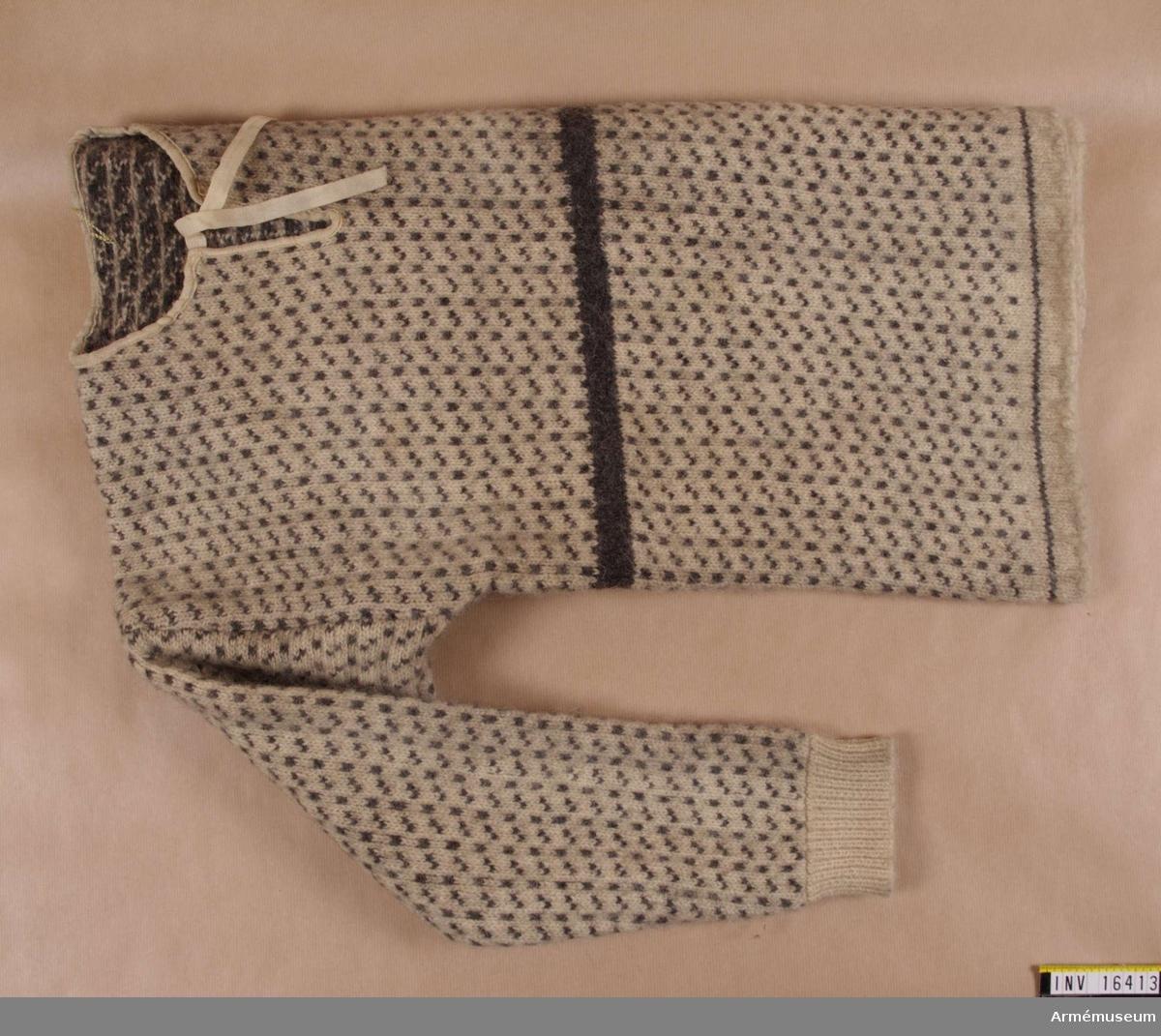 Sjömanströja, Island.Sjömanströja eller islandströja stickad av naturvit islandsull med mönster i grått. Mönstret består av enkla mönstergrupper vilka täcker hela ytan. På avigsidan bildas ett flotterande garnskickt som gör plagget varmare och binder elastciteten. Plagget håller på så sätt formen bättre. Framtill på plagget, i brösthöjd löper en 2,5 cm bred bård av grått garn. Bandkantat halssprund med ylleband, vilka löper fritt (18 cm) för fastknytning.KONS  Tvättad 1987-09 /AA.Tröjan kom till AM 1943-09-13 från Arméförvaltningens Intendenturdepartements modellkammare. Denna tröja benämns också norsk och den har samma utseende som AM 16412. Se vidare: Stickat och virkat i nordisk tradition. Österbottens museum, 1984, sida 10: tröjor.