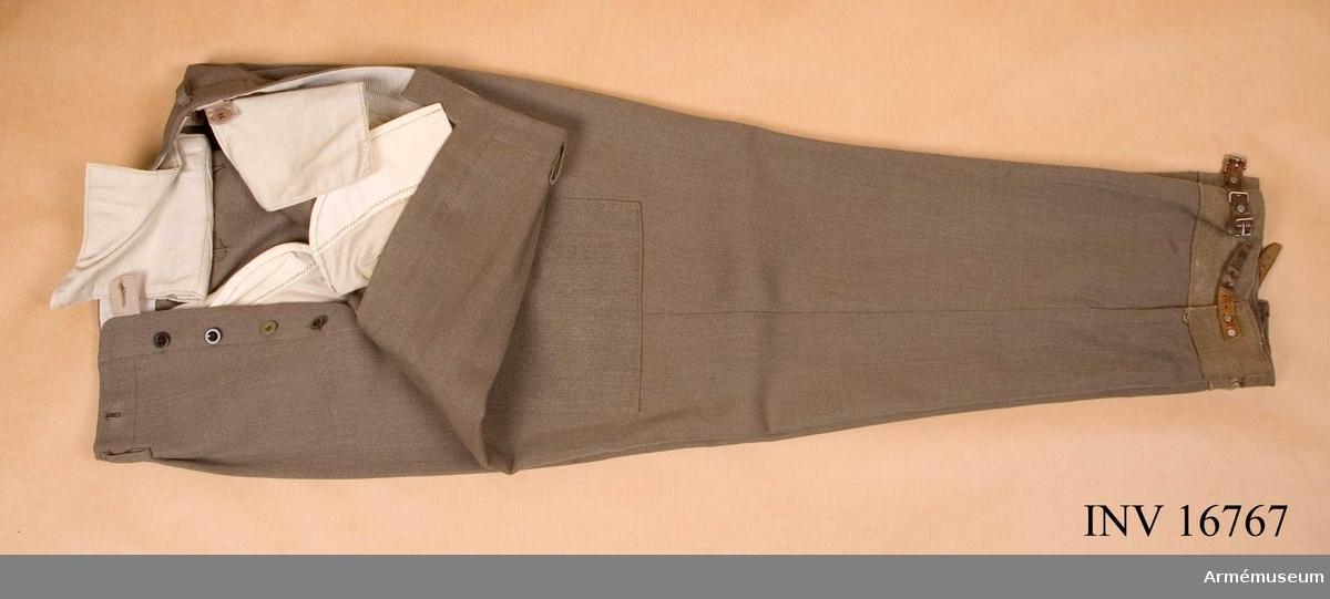 Förändringsmodell. Av gråbrungrönt yllediagonal, försedda med fast damask nedtill och påsydda stora fickor vid sidorna försedda med spetsiga lock. Sidfickor och bakfickor och med hällor i midjan. Stroppar och knappar för hängsle.