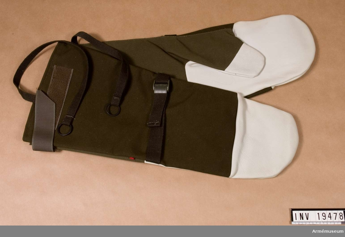 Tumhandskarna bärs med löstagbara fodervantar av ullfrotté. Handskens slityta är av vattenavvisande getskinn, överdel och krage av vindtät och vattenavvisande textil. Handsken har åtdragsrem vid handleden och reglerbar krage. Finns i tre storlekar.